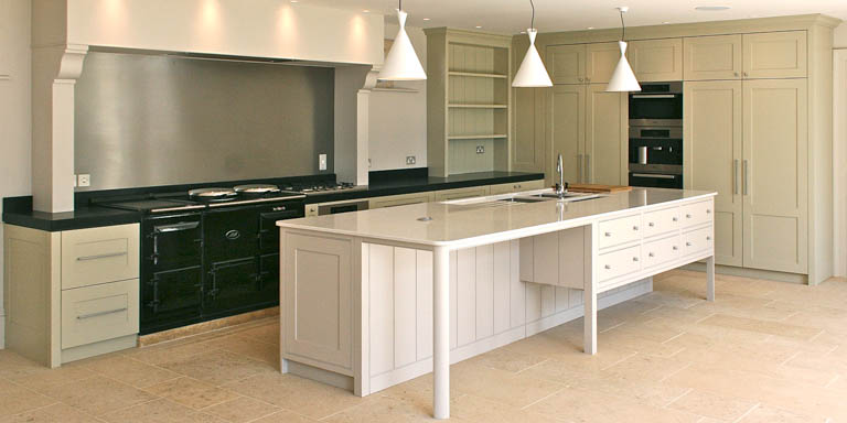 A kitchen project in Tetbury, Gloucestershire, featuring a large central island incorporating sinks, storage and white goods.